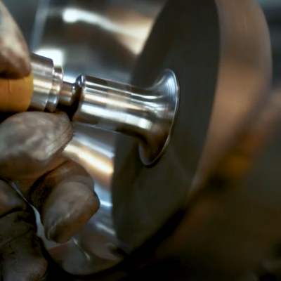 A HOLLOWAY employee grinds metal.
